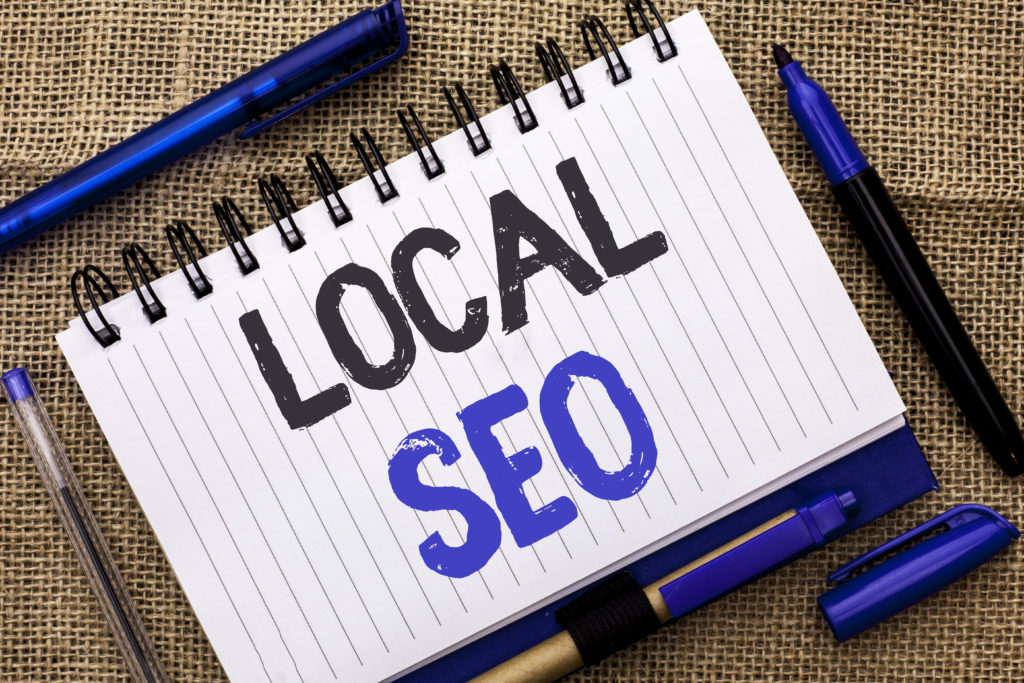 Conceptual hand writing showing Local Seo. Business photo showcasing Search Engine Optimization Strategy Optimize Local Find Keywords written Notebook Book jute background Pens next to it.